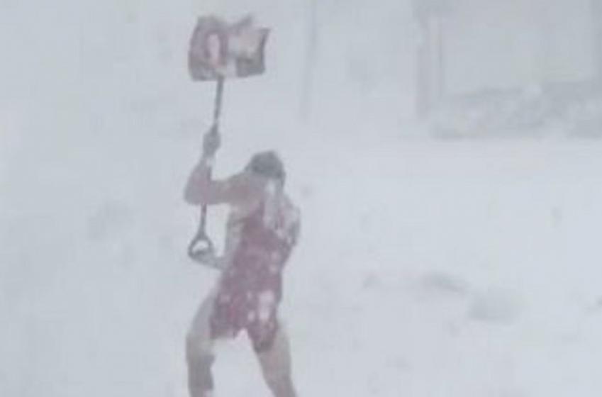 High school wrestler shovels snow in nothing but his wrestling gear.
